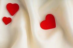 Czerwoni drewniani dekoracyjni serca na białym jedwabniczym tle. Zdjęcia Royalty Free