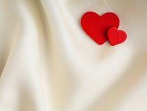 Czerwoni drewniani dekoracyjni serca na białym jedwabniczym tle. Zdjęcie Stock