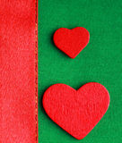Czerwoni drewniani dekoracyjni serca na zielonym sukiennym tle Zdjęcie Royalty Free
