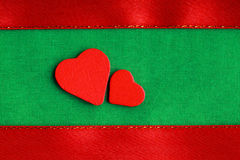 Czerwoni drewniani dekoracyjni serca na zielonym sukiennym tle Zdjęcia Royalty Free