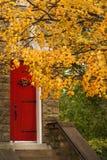 Czerwoni drzwi i pomarańcze jesieni liście Fotografia Royalty Free