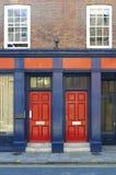 Czerwoni drzwi na budynku Zdjęcia Stock