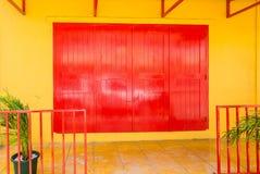 Czerwoni drzwi na kolor żółty ścianie Zdjęcie Stock