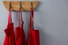 Czerwoni fartuchy wiesza na haczyku fotografia royalty free