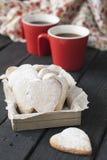 Czerwoni filiżanki i ciastka serca na czarnym tle Zdjęcie Royalty Free