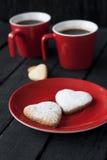 Czerwoni filiżanki i ciastka serca na czarnym tle Obrazy Stock