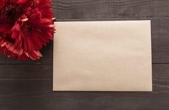 Czerwoni gerbera kwiaty, karta i są w drewnianym tle Obrazy Royalty Free