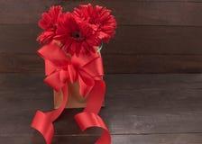 Czerwoni gerbera kwiaty z faborkiem są w torbie na drewnianych półdupkach, Fotografia Royalty Free