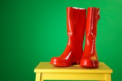 Czerwoni gumowi buty na stolec Zdjęcia Stock