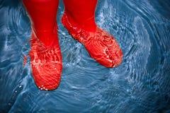 Czerwoni gumowi buty w wodzie Zdjęcia Stock