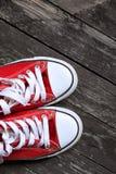 Czerwoni gym buty na drewnianym tle Sneakers na drewnianej podłoga Zdjęcia Royalty Free
