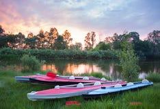 Czerwoni i błękitni kajaki blisko rzeki w pięknej naturze przy zmierzchem Obrazy Royalty Free
