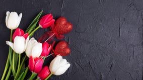 Czerwoni i biali tulipanów kwiaty i decortive serca na czarnym tekscie Fotografia Royalty Free