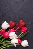 Czerwoni i biali tulipanów kwiaty i decortive serca na czarnym tekscie Obraz Stock