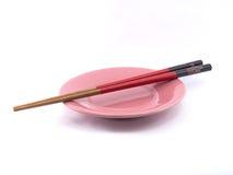 Czerwoni i czarni chopsticks i menchia talerz odizolowywający na białym tle Fotografia Stock
