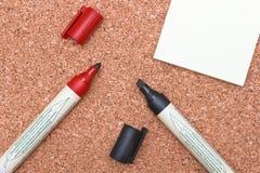 Czerwoni i czarni markiery z białą kleistą notatką na korku Obraz Stock