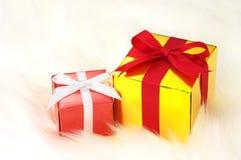 Czerwoni i złociści prezenty na biel imitaci futerku. Obrazy Stock