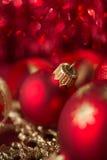 Czerwoni i złoci xmas ornamenty na jaskrawym bokeh tle Obraz Stock