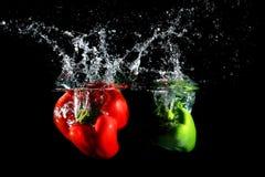 Czerwoni i zieleni pieprze spada w wodę, na czarnym tle Zdjęcia Stock