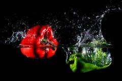 Czerwoni i zieleni pieprze spada w wodę, na czarnym tle Obrazy Stock