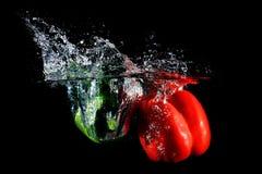 Czerwoni i zieleni pieprze spada w wodę, na czarnym tle Obraz Royalty Free