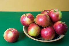 Czerwoni jabłka w glinianym pucharze na zielonym i żółtym tle obraz stock
