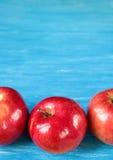 Czerwoni jabłka na błękitnym drewnianym stole Zdjęcie Royalty Free