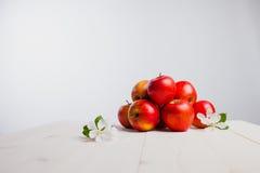 Czerwoni jabłka na białym drewno stole fotografia royalty free