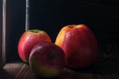 Czerwoni jabłka na ciemnym wieśniaka stole Fotografia Stock