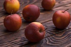 Czerwoni jabłka na drewnianym stole, selekcyjna ostrość Fotografia Stock