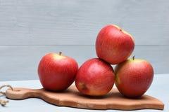 Czerwoni jabłka na tnącej desce Obrazy Royalty Free