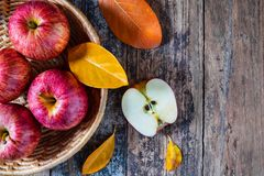 Czerwoni jabłka w koszu Na starym drewniany stół zdjęcia royalty free