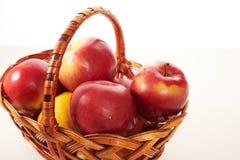 Czerwoni jabłka w koszu odizolowywają Fotografia Stock