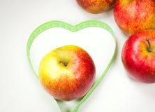 Czerwoni jabłka z pomiarową taśmą tworzy kierowego kształt zdjęcia stock