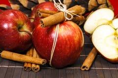 Czerwoni jabłka i cynamonowi kije fotografia stock