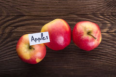 Czerwoni jabłka na drewnianym tle Obraz Stock