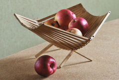 Czerwoni jabłka w drewnianym koszu na zielonym tle Fotografia Stock