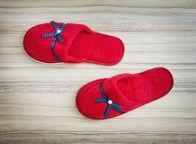 Czerwoni kapcie z błękitnym faborkiem na drewnianym tle, wibrującym Fotografia Royalty Free