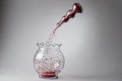 Czerwoni koraliki spada w szklaną wazę Fotografia Royalty Free