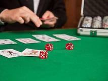 Czerwoni kostka do gry i karta do gry na stole Obrazy Royalty Free
