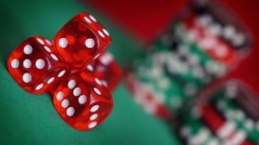 Czerwoni kostka do gry i kasyno układy scaleni na zielonym stole Obraz Stock