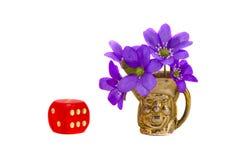 Czerwoni kostka do gry i mosiężna waza z fiołkowymi kwiatami Zdjęcie Royalty Free