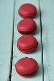 Czerwoni macarons na błękitnym wieśniaka stole Zdjęcie Stock