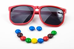 Czerwoni okulary przeciwsłoneczni i kolorowi candys Zdjęcie Stock