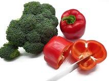 Czerwoni pieprze i brokuły uwalniający na białym tle fotografia stock