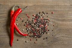 Czerwoni pieprze i groch pieprzą na drewnianym stole Fotografia Royalty Free
