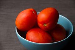 Czerwoni pomidory na błękitnym pucharze zdjęcia stock