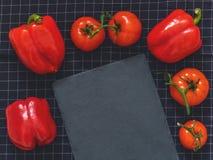 Czerwoni pomidory na gałąź, czerwony pieprz, tnącej deski łupek na bla Fotografia Royalty Free