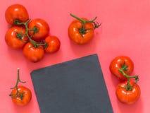 Czerwoni pomidory na gałąź, tnącej deski łupek na różowym backgrou Obrazy Royalty Free