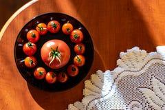 Czerwoni pomidory w czarnym talerzu na kuchennym stole obok Notepad zdjęcia royalty free